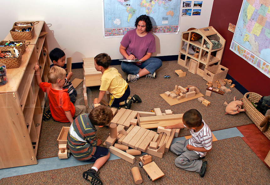 Preschool students playing with building blocks while teacher observes.