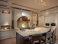 The unique hammered copper stove hood and gradations of green tile backsplash in a kitchen that combines classic with modern elements.