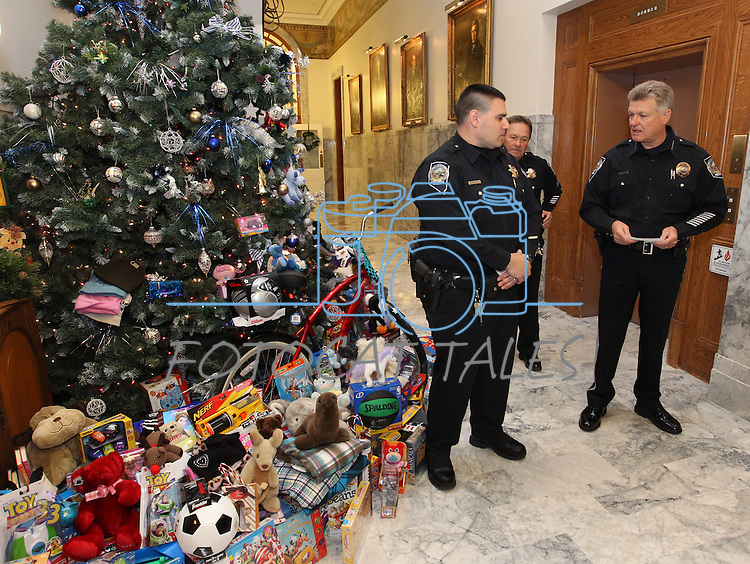 Public Safety Director Jerry Hafen, far right, and Capitol Police Officer Mike Rubio and Sgt. Randy Smith (rear) acknowlege more than a dozen state agencies who participated in this years' Toys for Tots toy drive organized by the Capitol Police at the Capitol in Carson City, Nev. on Friday, Dec. 17, 2010. .Photo by Cathleen Allison