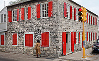 A woman walks past a stone house featuring colourful red window shutters in  New Providence, Nassau, Bahamas. photo by Trevor Collens