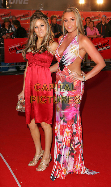 NIKKI GRAHAME & MICHELLE SCOTT-LEE.Red carpet arrivals at the Vodafone Live Music Awards at Earls Court, London, England. .September 19th, 2007.full length big brother heaton red dress hand on  hip pink floral print gold strappy sandals halterneck .CAP/ROS.©Steve Ross/Capital Pictures