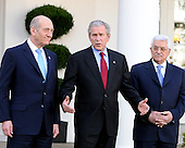 Washington, DC - November 28, 2007 -- United States President George W. Bush, center, makes a statement in the Rose Garden of the White House in Washington, D.C. as Prime Minister Ehud Olmert of Israel, left, and President Mahmoud Abbas of the Palestinian Authority, right, look on, Wednesday, November 28, 2007.   The leaders were concluding 3 days of meetings seeking ways to reengage the peace process between Israel and the Palestinians..Credit: Ron Sachs / CNP