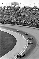 INDIANAPOLIS, IN - MAY 31: A group of cars race through Turn 1 during the Indianapolis 500 USAC Indy Car race at the Indianapolis Motor Speedway in Indianapolis, Indiana, on May 31, 1986.