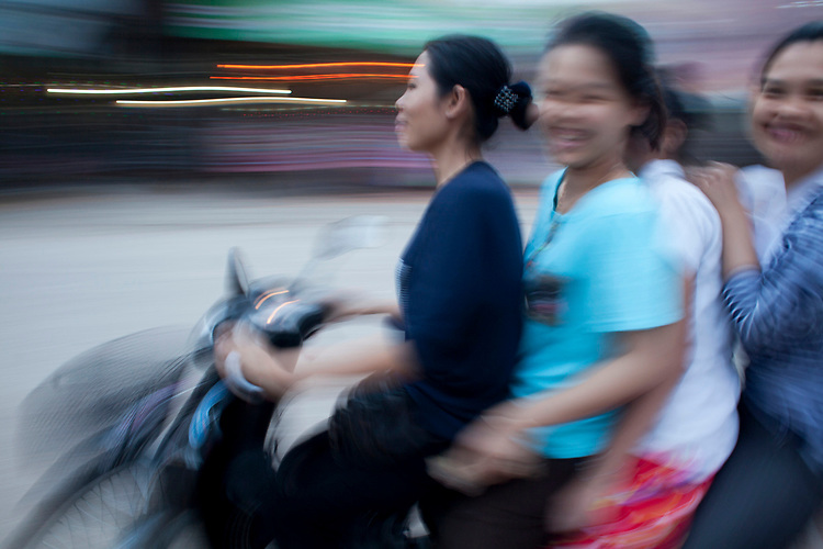 Motion blurred image of three woman on a motorbike in Phnom Penh, Cambodia. <br /> <br /> Photos &copy; Dennis Drenner 2013.