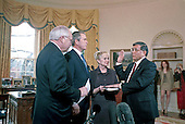 United States President George W. Bush, center left, observes as US Vice President Dick Cheney, left, swears in Norman Mineta, right, as US Secretary of Transportation in the Oval Office of the White House 08 February 2001 in Washington DC.  Mineta's wife Deni holds the bible. <br /> Credit: Jamal A. Wilson / Pool via CNP