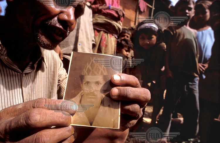 © Dermot Tatlow / Panos Pictures..NEPAL..A father shows a picture of his son, one of Nepal's disappeared.