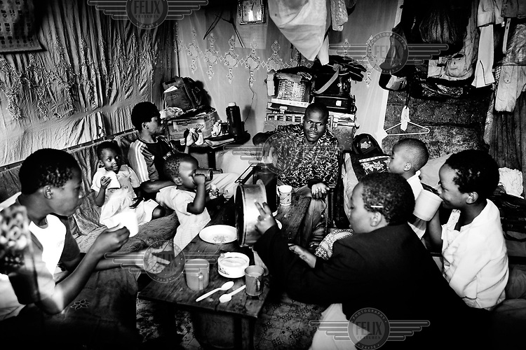 The Odongo family eating breakfast in their house in Kibera. Clockwise from left: Lavenda, Naomi, Meshak, Michelle, Augustin Odongo, Cynthia, Eunice and Clarissa. Homes in Kibera are made out of corrugated tin, mud, cardboard and plastic and consist of one room that serves as a kitchen, living room, and bedroom. Most homes are about 3 metres square and have an average of five people living in them. Over 25 percent of Nairobi's population live in Kibera, an area that covers less than one percent of the city. Although the population of the slum is over one million, it is recognised officially as a 'squat', or illegally occupied land, which allows the government to ignore the basic needs of the inhabitants.