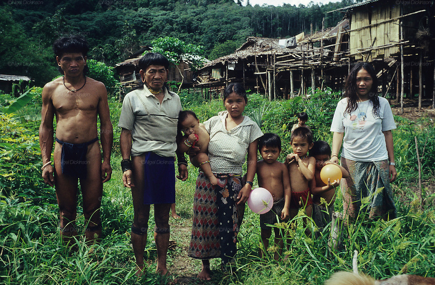 1989: Penan natives. Baru (LHS), Banai Tebai (2nd LHS) and Rasa (RHS) and extended family. Living a semi-nomadic lifestyle.Their 'sulap' temporary settlement, made from wood, bamboo and rattan is behind. Long Tedang, Sarawak, Borneo.<br />