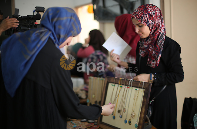 Palestinians attend an exhibition for handicrafts products in Gaza city, on August 15, 2017. Photo by Mohammed Asad