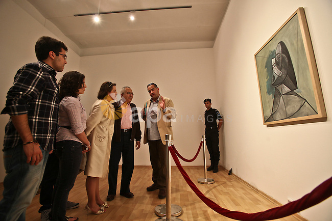 "Palestinian Prime minister Salam Fayyad (C-L) and his family look at Picasso's 1943 canvas ""Buste de Femme"" which was lent by The Van Abbe museum in Eindhoven to the Palestinian Art Academy museum in the West Bank city of Ramallah on June 24, 2011. Photo by Fadi Arouri / POOL"