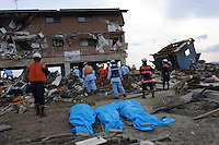 three bodies lie in the fore-ground as a search and rescue team look through the remains of a houses in the town of Natori, after the Tsunami devastated the entire pacifc coastline of Japan after the earthquake and tsunami devastated the area Sendai, Japan.<br />