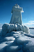 Lower harbor breakwall lighthouse in Marquette Michigan on Lake Superior after a three day storm in January 1978.