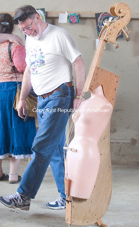 "CORNWALL, CT - 21 APRIL 2007 - 042107JW05.jpg -- Bob Collins of Harwinton chuckles as he walks past the sculpture of Tim Prentice entitled ""A Little Night Music"" during the Annual Art at the Dump art show at the Cornwall Town Garage and Transfer station Saturday afternoon. Jonathan Wilcox Republican-American"
