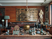 "Above the sofa, custom-made by Hakan Ezer, hangs a painting by contemporary artist Canon Tolon. The statue is ""Two Sisters"" by Kai Nielsen. The coffee table is from Afganistan and the chandelier is early twentieth century from Belgium"