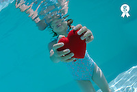Girl (6-7) holding heart shaped symbol in swimming pool, underwater view (Licence this image exclusively with Getty: http://www.gettyimages.com/detail/sb10065474dm-001 )