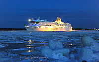 Tallink Romantika steams through the icy channel in twililght where the Daugava river meets the Gulf of Riga, Latvia.
