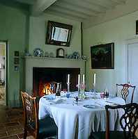 A circular table draped in a white cloth and set infront of a warm fire is laid for a simple lunch