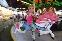NWA Democrat-Gazette/ANDY SHUPE<br /> Jolie Vaughn, 5, of West Fork smiles Thursday, Sept. 3, 2015, as she rides the merry-go-round during the Washington County Fair at the county fairgrounds in Fayetteville.