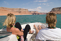 Adult couple sitting on front of ski boat on Lake Powell, Utah