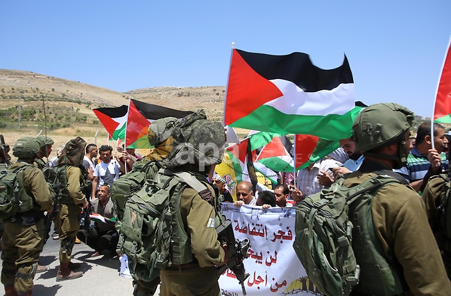 Palestinian protesters argue with Israeli soldiers during a demonstration in solidarity with Palestinian hunger-striking prisoners held in Israeli jails, at Israeli checkpoint of Hawara, near the West Bank city of Nablus, on May 11, 2017. Photo by Ayman Ameen