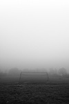 A simple football goal on an empty abandoned field on a foggy morning