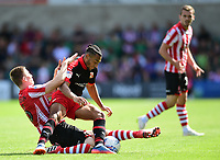 Swindon Town's Keshi Anderson is tackled by Lincoln City's Scott Wharton<br /> <br /> Photographer Chris Vaughan/CameraSport<br /> <br /> The EFL Sky Bet League Two - Lincoln City v Swindon Town - Saturday 11th August 2018 - Sincil Bank - Lincoln<br /> <br /> World Copyright &copy; 2018 CameraSport. All rights reserved. 43 Linden Ave. Countesthorpe. Leicester. England. LE8 5PG - Tel: +44 (0) 116 277 4147 - admin@camerasport.com - www.camerasport.com