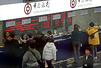 Passengers change money at The Bank of China in the departure hall of the Beijing International Airport, China..
