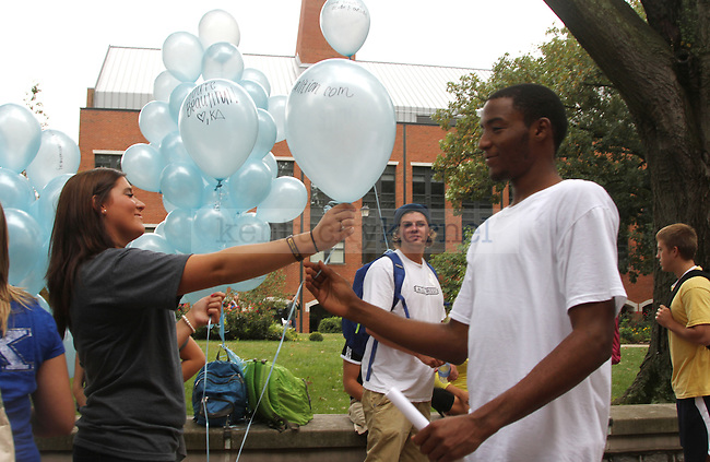 "Kappa Delta secretary Casey Jackson hands a balloon to undeclared freshman Jaquail Fowler. Women from Kappa Delta sorority handed out balloons, pens, stickers and magnets in honor of International Women's Friendship Month to boost women's confidence, outside of White Hall Classroom Building in Lexington, Ky., Sept. 20, 2011. While giving balloons to men, the women told them to ""be nice to girls."" Photo by Becca Clemons 