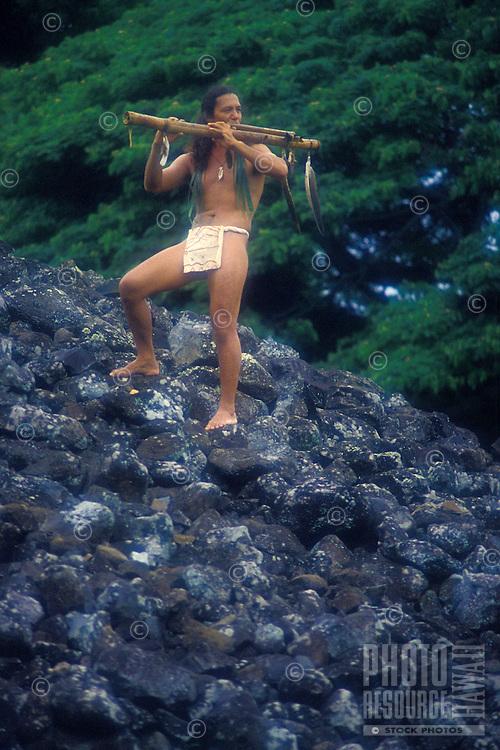 Hawaiian man playing flute at ancient temple, Heiau, site. Oahu