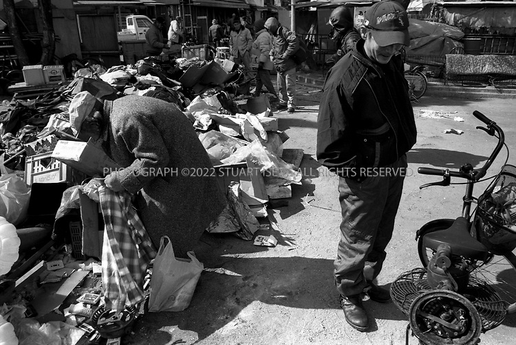 Osaka, Japan..Homeless men sort though garbage looking for things for themsleves or for resale in Osaka's Kamagaeski neighborhood, often called Japan's biggest slum...All photographs ©2003 Stuart Isett.All rights reserved.This image may not be reproduced without expressed written permission from Stuart Isett.