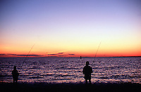 The silhouettes of two men as they fish from the shore, looking out over the sunset horizon. Menemsha, Massachusetts.