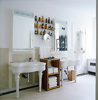 In the bathroom a collection of antique apothecary jars is displayed on glass shelves between a matching pair of vintage wash basins