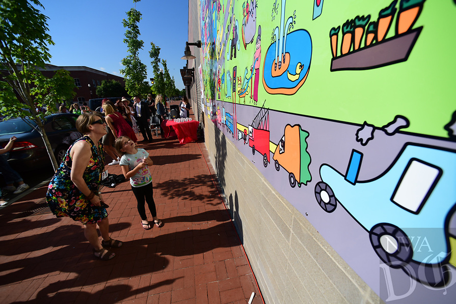 Northwest Arkansas Democrat Gazette/SPENCER TIREY Heather Collier, board president of Art Feeds talk to R.E. Baker Elementary 2nd grader Suekie Hamilton about the mural students  at the elementary school unveiled Tuesday May 16, 2017,  on the side of the Walmart Neighborhood Market in downtown Bentonville. Arts Feeds with help of sponsorships by the Sharon and Terry Berkstresser Fund, Walmart Marketing Department and the Walmart Museum worked with the school to create the mural. It is the first mural Art Feeds has done in Bentonville and the 30 Mural the group has done in Northwest Arkansas.