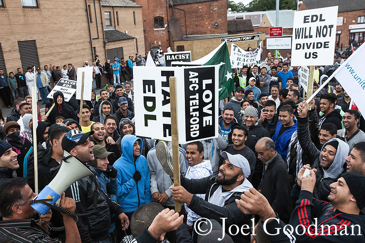 © Joel Goodman - 07973 332324 . 13/08/2011 . Shropshire , UK . Counter protesters use shoes to smash a picture of prominent EDL member, Guramit Singh . Approximately 300 EDL supporters demonstrate against a paedophile ring in the small Telford town of Wellington . The group had planned to march, however the Home Secretary has imposed a ban on all marches in the area just days after riots have swept across England. A counter-demonstration has attracted about 300 people . Photo credit : Joel Goodman