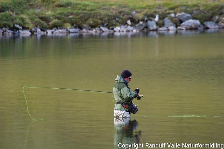 Mann fisker med flue i Rekvikvannet på Sværholt. ----- Man fly fishing in large lake.