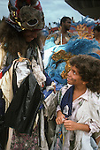 Rio de Janeiro, Brazil. Samba dancers during the carnival parade; boy and his mother in ragged poverty theme costumes.