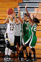 6 February 2010:  FIU's Elisa Carey (12) passes the ball while being defended by North Texas' Raquel Cuffie (11) and Niq'ky Hughes (23) in the first half as the FIU Golden Panthers defeated the North Texas Mean Green, 72-55, at the U.S. Century Bank Arena in Miami, Florida.