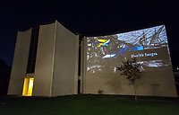 """Opening reception of the inaugural Ettinger Projected Poetry and Art Project: """"New"""" World(s) which is a collaboration by Wanlass Artist in Residence Kenyatta A.C. Hinkle, media artist Keith Skretch, and ARTS290: Art Outside the Bounds students. The images and text are projected onto the south wall of Herrick Chapel and the reception was outside the Academic Commons, Dec. 7, 2017. Presented by Oxy Arts and CDLA.<br /> <br /> Students conducted research at Special Collections at Occidental College and amassed personal archives from prompts pertaining to personal narratives and images that haunted, challenged and provoked them. Students implemented interrupting the aesthetic of the didactic as a colonial tool of codifying. They also interviewed one another, and the residue of these questions and answers flicker in and out of the imagery. The context of the questions were formed by what roles we play within our family histories, how we absorb information as forms of truth and what does it mean to be an instrument of interruption, remixing, and restructuring narratives and historical and contemporary storytelling. Utilizing found imagery, objects and images from Herrick Chapel, these investigations weave in and out of one another, reminiscent of collage or a palimpsest of multiple interrogations and considerations of the truth.<br /> The Ettinger Projected Poetry and Art Project is a public art project that infuses the written word and images into everyday moments around campus. Presented nightly for several hours during reading days and finals week each semester through spring 2020, the rotating exhibitions will project provocative and intellectual work on frequently viewed spaces on campus, inspiring deep collaborations between the arts and digital sciences and building pathways and partnerships that mirror our increasingly pluralistic world.<br /> The Wanlass Artist in Residence is Occidental's annual residency program that allows an artist to investigate aspects of t"""