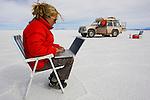 Bolivia, Altiplano, woman working on laptop in Salar de Uyuni, world's largest salt pan