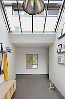 The studio come gallery gets plenty of natural light provided by the skylight. Artworks are displayed on wall shelves.