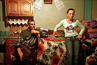 ROMANIA / Maramures / Budesti / 28.08.2006..Anuta Tibil, 16, and her father, Vasilya, 47, watch satellite television. In the lead up to joining the European Union in 2007, Romania underwent dramatic technolgical changes and nowhere is this more evident than in Maramures. Satellite television descended upon the region in 2006, when companies finally made it cheap enough for peasants to sign up for the basic 100 channel package. Now, even traditional, carved, wooden homes are marked by small satellite dishes affixed to their front porches or rooves. The internet is sure to follow soon. Maramures has experiended more change since the year 2000 than in the entire previous millenium...© Davin Ellicson / Anzenberger