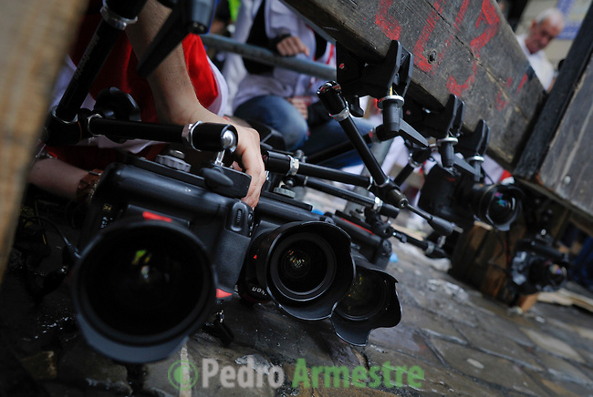 "A photographer placed cameras for  Miura bulls ""encierro"" during the second San Fermin Festival bull run, on July 8, 2012, in Pamplona, northern Spain. The festival is a symbol of Spanish culture that attracts thousands of tourists to watch the bull runs despite heavy condemnation from animal rights groups . (c) Pedro ARMESTRE"