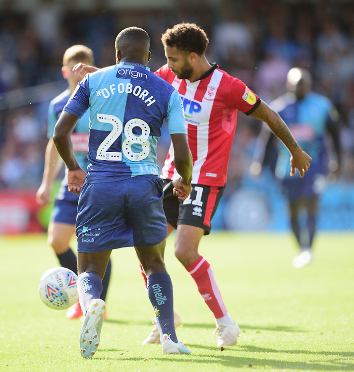 Lincoln City's Bruno Andrade vies for possession with Wycombe Wanderers' Nnamdi Ofoborh<br /> <br /> Photographer Andrew Vaughan/CameraSport<br /> <br /> The EFL Sky Bet League One - Wycombe Wanderers v Lincoln City - Saturday 7th September 2019 - Adams Park - Wycombe<br /> <br /> World Copyright © 2019 CameraSport. All rights reserved. 43 Linden Ave. Countesthorpe. Leicester. England. LE8 5PG - Tel: +44 (0) 116 277 4147 - admin@camerasport.com - www.camerasport.com