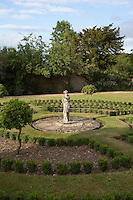 A statue of a woman in the centre of a formal garden in the grounds of Lower Slaughter Manor, now a hotel in Gloucestershire