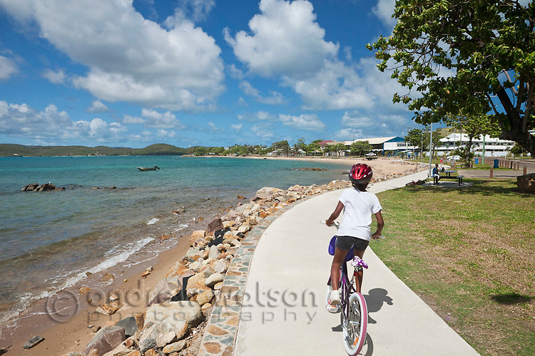 Kids ride their bikes along the Victoria Parade esplanade.  Thursday Island, Torres Strait Islands, Queensland, Australia