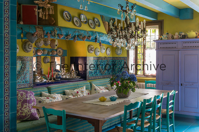 The kitchen/dining area features a turquoise and yellow painted ceiling and walls to match which are lined additionally in patterned turquoise tiles