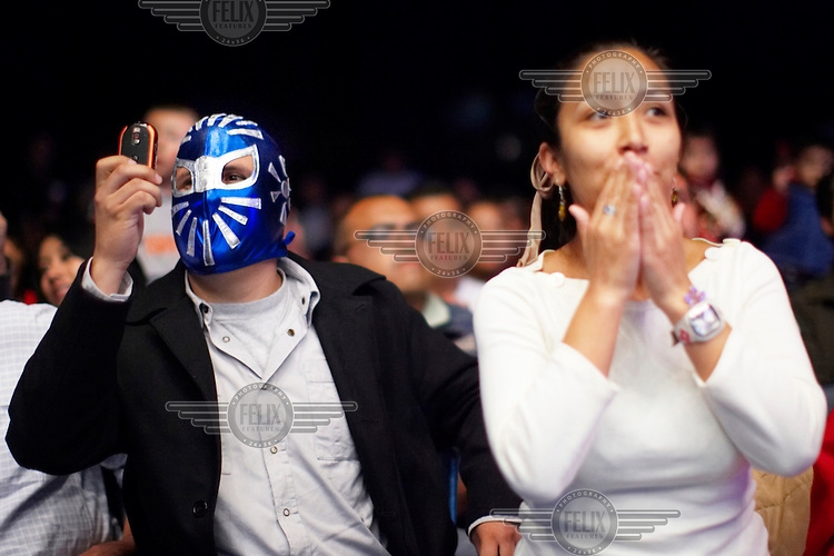 Spectators, one of whom is wearing a Luchador's (fighter's) mask, watch the match. Lucha Libre is a style of wrestling started in Mexico in 1933. The name means Free Fight, and matches tend to be focussed on spectacle and theatre with fans cheering for their favourite characters, who wear masks while jumping from the ropes, flipping opponents, and occasionally crashing into the crowd..©Jacob Silberberg/Panos/Felix Features.