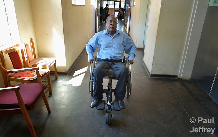 Sunny Nyamandwe moves along a hallway at the National Rehabilitation Centre in Ruwa, Zimbabwe. The Centre assembles and fits wheelchairs provided by the Jairos Jiri Association with support from CBM-US, and Nyamandwe is one of the beneficiaries of the program. His legs remain paralyzed after an automobile accident more than two decades ago.