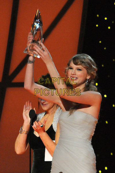 Taylor Swift.The 45th Annual CMA Awards, Country Music's Biggest Night, held at Bridgestone Arena, Nashville, Tennessee, USA..November 9th, 2011.on stage half length grey gray strapless dress award trophy winner arms in air .CAP/ADM/LF.©Laura Farr/AdMedia/Capital Pictures.