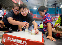 NWA Democrat-Gazette/JASON IVESTER<br /> Carter Brewer (from left), Henry Sims and Jaden Park, all Westside Elementary fifth-graders, work on their maze game Wednesday, May 10, 2017, during the Rogers Schools REACH fair, titled Game-On REACH Arcade, inside the Rogers Activity Center. Fifth-graders from the REACH program -- the district's gifted and talented program -- worked to create arcade games from various materials, predominatly cardboard.
